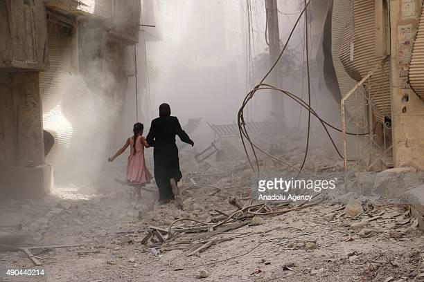 A woman and a kid run through the smoke after an airstrike staged by Syrian regime forces to the opposition residential areas in Duma district in the...