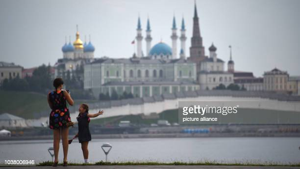 A woman and a little girl stand at the embrankment of the River Volga in front of a backdrop of the Qol Sharif mosque in the city of Kazan Russia 11...