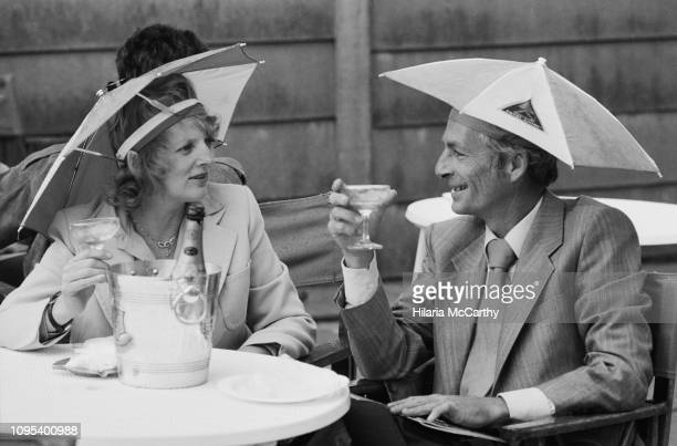 Woman and a man, both wearing umbrella hats, drink a glass of champagne while attending The Championships at the All England Lawn Tennis and Croquet...