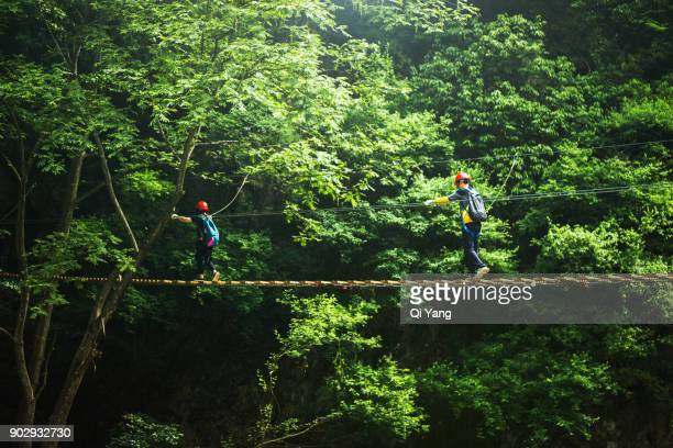 A woman and a man crosses an exposed suspension bridge, China