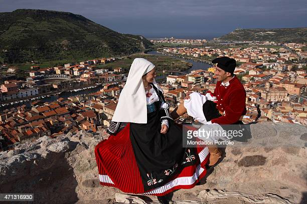 A woman and a man in a folk costume sitting on the parapet of the Malaspina Castle on the top of the Serravalle hill Bosa Italy April 2006
