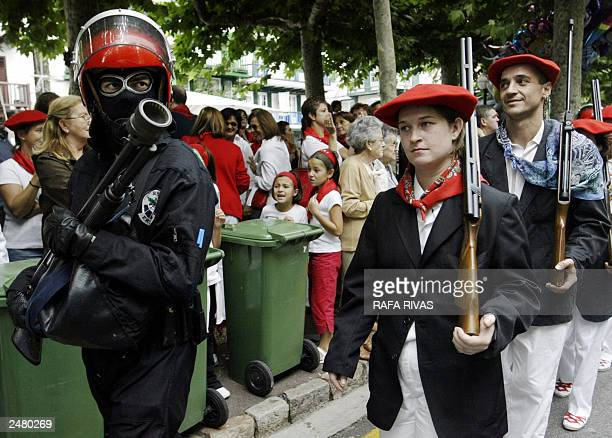 A woman and a man members of the 'Jaizkibel' group who participate in the 'Alarde' festive parade in Hondarribia Basque country march with guns close...
