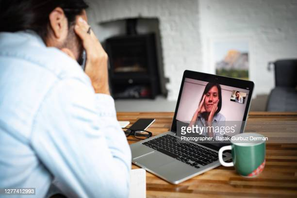 a woman and a man video teleconferencing, the woman is smiling - negative emotion stock pictures, royalty-free photos & images