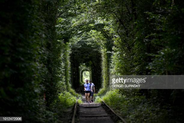 A woman and a man walk along former railway tracks surrounded by arches of intertwined trees in the socalled 'Tunnel of Love' near the Ukrainian...