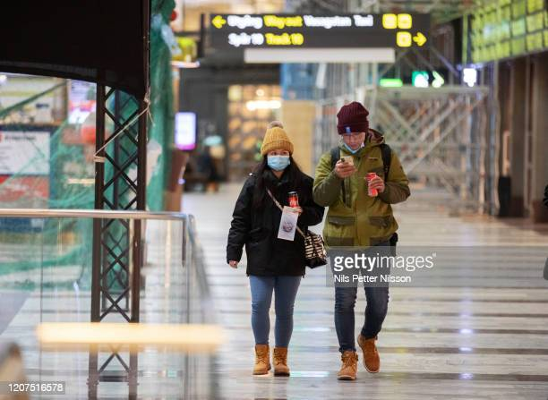 Woman and a man wearing face masks at Stockholm Central Station on March 17, 2020 in Stockholm, Sweden. Coronavirus has spread to over 156 countries...