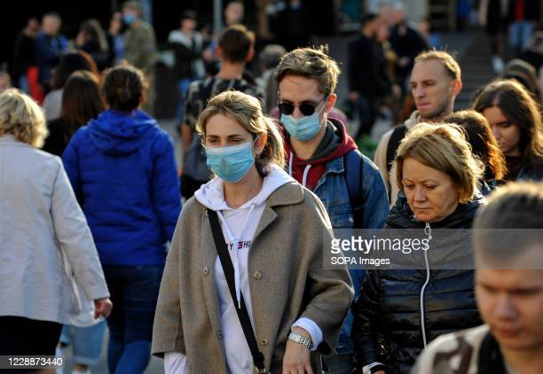 Woman and a man wearing protective masks as a precaution, walking down the street in Kiev. For four days in a row, Covid 19 case have been at record...