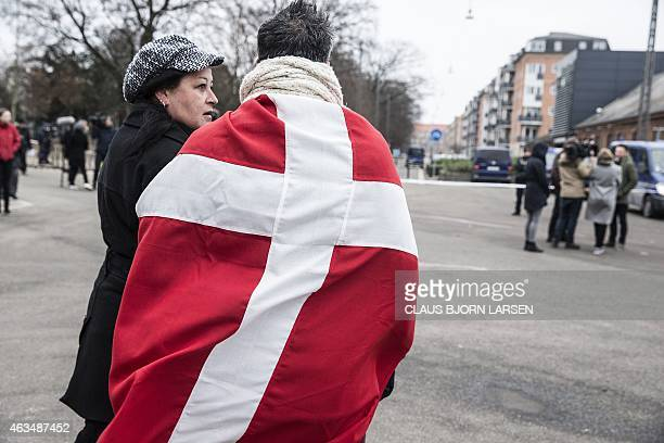 A woman and a man wearing the danish flag stand outside the main Synagogue in Copenhagen on February 15 2015 following two fatal attacks in the...