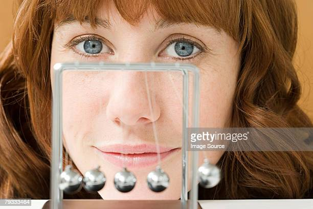 A woman and a newtons cradle