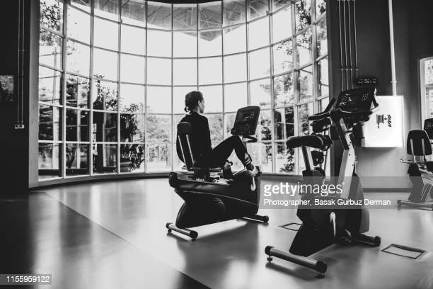 A woman and a personal trainer / coach practicing on indoor exercise bikes in a health club / fitness center