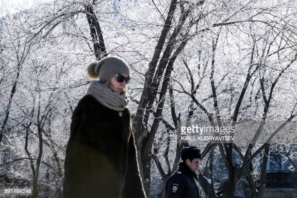 A woman and a policeman walk past snowcovered trees in Baikonur city near the Russian leased Kazakh Baikonur cosmodrome on December 13 2017 The...