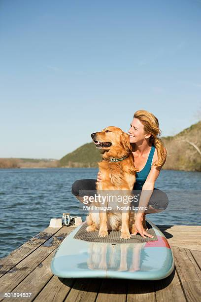 A woman and a retriever dog on a paddleboard on the jetty.
