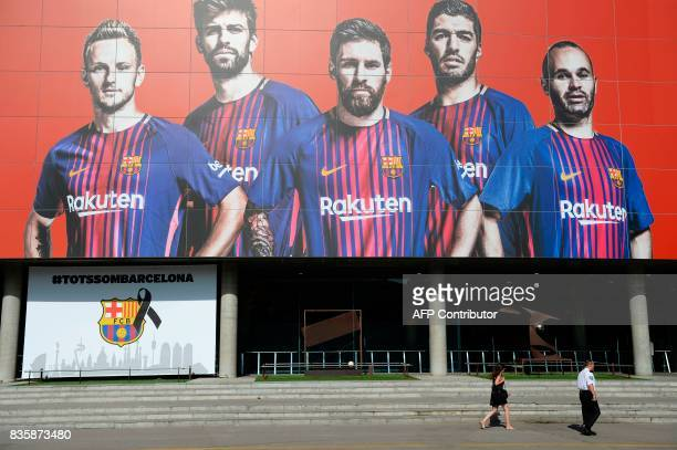 A woman and a security member pass by the FC Barcelona logo with a black ribbon and a message reading 'We are all Barcelona' and a giant picture of...