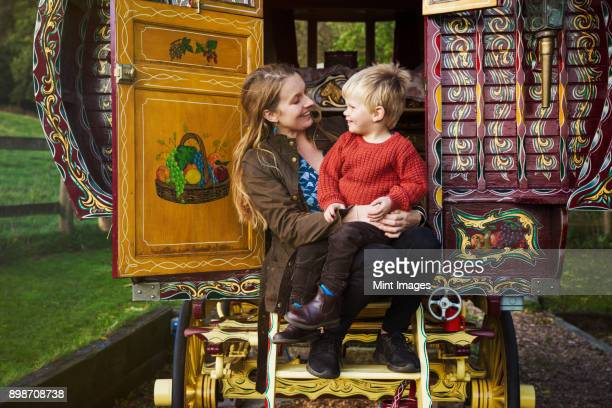 A woman and a small boy seated on the steps of a bow top caravan painted in a traditional style.