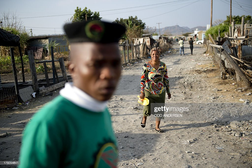 A woman and a union representative walk the dirt path in the Nkaneng shantytown next to the platinum mine, run by British company Lonmin, in Marikana. On August 16, 2012, police at the Marikana mine open fire on striking workers, killing 34 and injuring 78, during a strike was for better wages and living conditions. Miners still live in dire conditions despite a small wage increase.