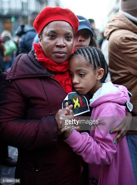 A woman and a young girl embrace as people gather to leave tributes at the Place de la Bourse following today's attacks on March 22 2016 in Brussels...