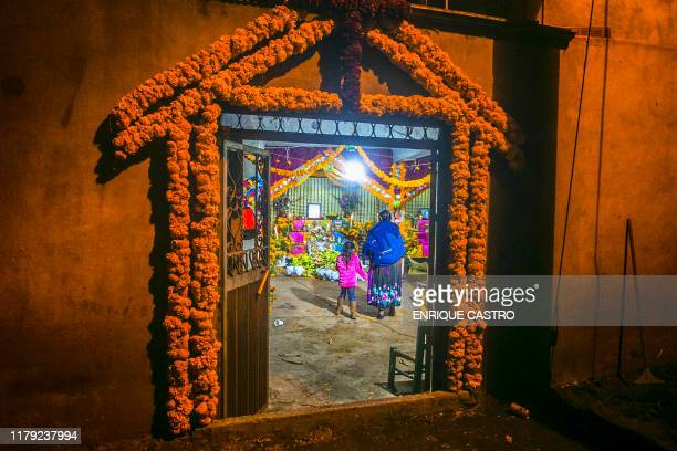 TOPSHOT A woman and a young girl look at offerings for the celebration of the Day of the Dead in Santa Fe de la Laguna village Quiroga municipality...