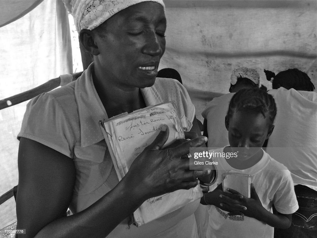 A woman and a young girl pray during a morning service at 'Eglise de Dieu Evangelic' March 24, 2013 in Kabic, Haiti.