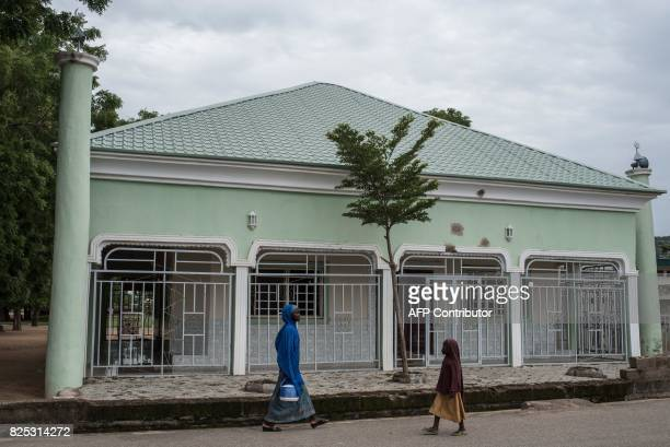 A woman and a young girl walk on August 1 2017 past the mosque that the leader of Boko Haram claimed during the occupation of Gwoza in northeastern...
