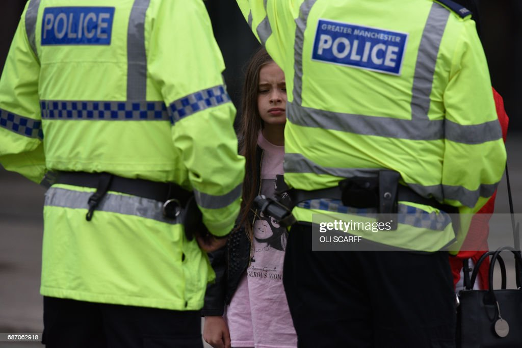 TOPSHOT - A woman and a young girl wearing a t-shirt of US singer Ariana Grande talks to police near Manchester Arena following a deadly terror attack in Manchester, northwest England on May 23, 2017. Twenty two people have been killed and dozens injured in Britain's deadliest terror attack in over a decade after a suspected suicide bomber targeted fans leaving a concert of US singer Ariana Grande in Manchester. / AFP PHOTO / Oli SCARFF