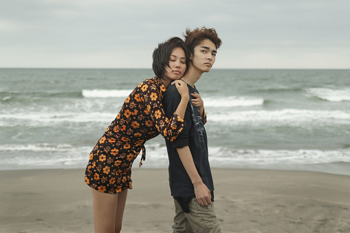 A woman and a young man are on the beach - gettyimageskorea
