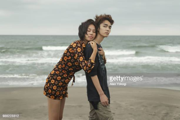 A woman and a young man are on the beach