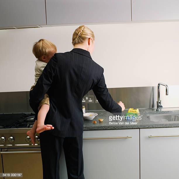 woman and baby at kitchen sink - working mother stock pictures, royalty-free photos & images