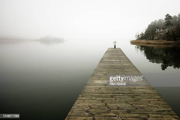 Woman and baby on pier over misty sea