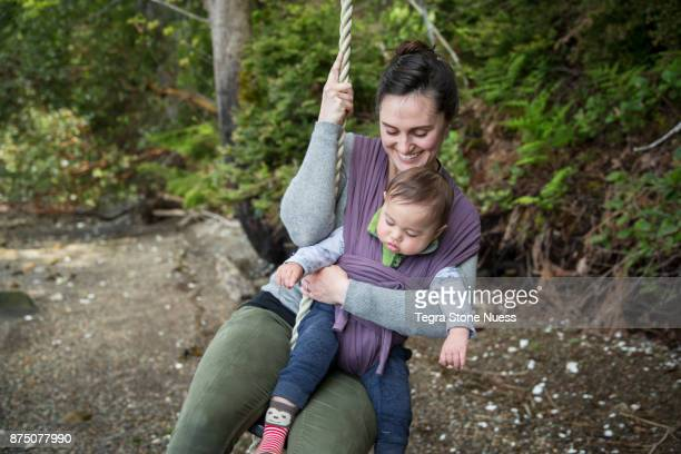woman and baby on rope swing - mom sits on sons lap stock pictures, royalty-free photos & images