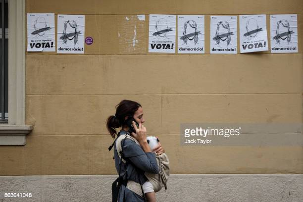 A woman and baby walks past Catalan proindependence posters on a wall on October 20 2017 in Barcelona Spain The Spanish government is to take steps...