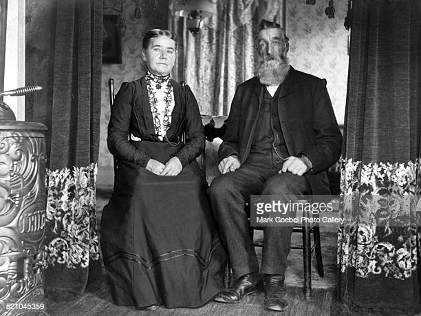 Woman and bearded man in chairs 1900s