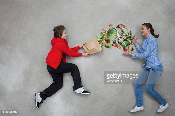 Woman and boy balancing vegetables
