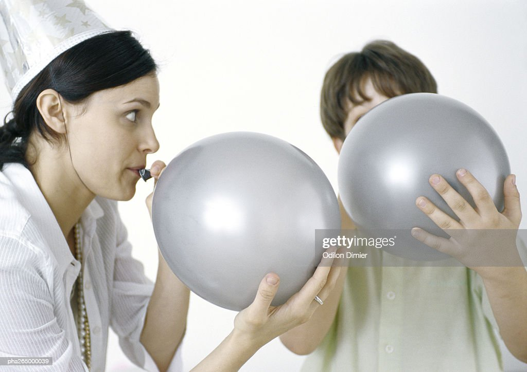 Woman and boy blowing up silver balloons : Stockfoto