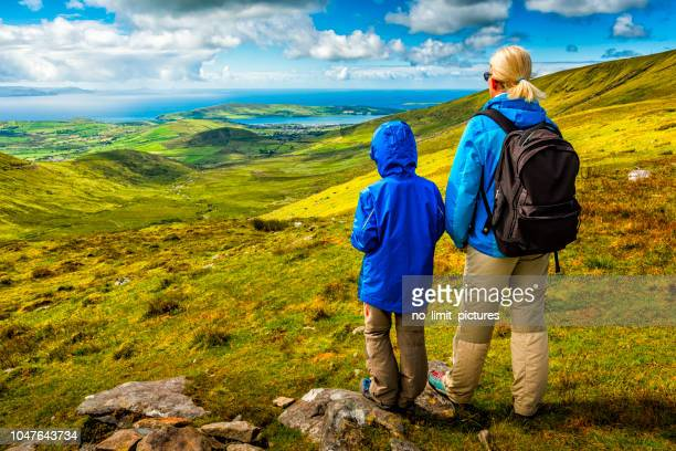 woman and boy hiking in ireland - ring of kerry stock photos and pictures