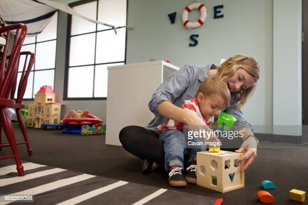 woman and boy playing with geometric puzzle box at preschool - nanny stock photos and pictures