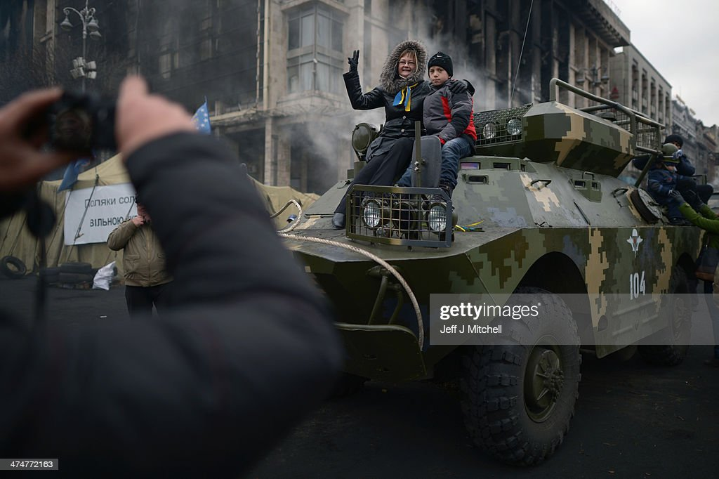 A woman and boy sit on top of a armored vehicle, to have her photograph taken in Independence Square, where dozens of protestors were killed in clashes with riot police last week on February 25, 2014 in Kiev, Ukraine. Ukraine's interim President Olexander Turchynov is due to form a unity government, as UK and US foreign ministers meet to discuss emergency financial assistance for the country.