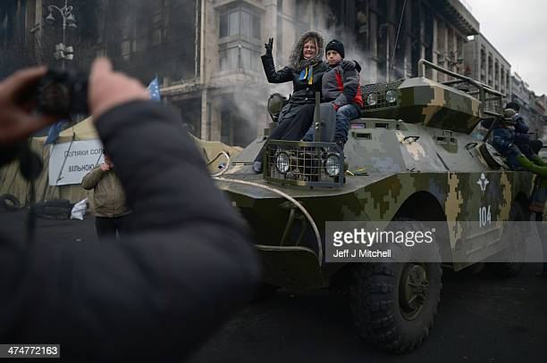 A woman and boy sit on top of a armored vehicle to have her photograph taken in Independence Square where dozens of protestors were killed in clashes...