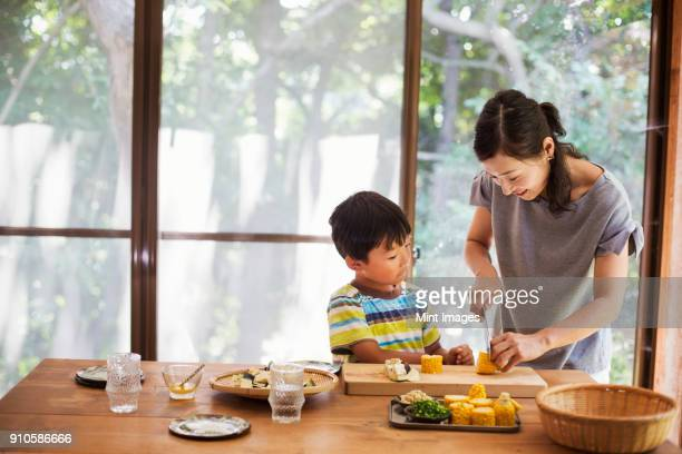 Woman and boy standing at a table, preparing corn on the cob, smiling.