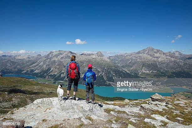 Woman And Boy With Dog Standing On Rock While Looking At Lake Silvaplana