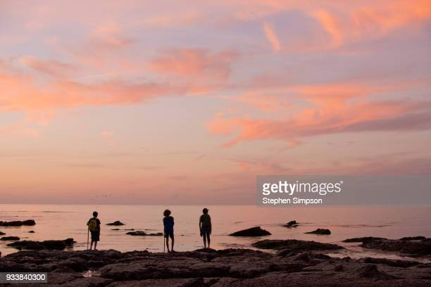Woman and boys explore tidal pools at sunset