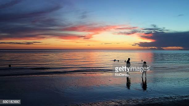 woman and boys stand in shallow surf as sun sets. - marco island stock pictures, royalty-free photos & images
