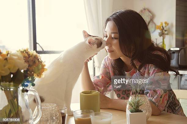 Woman and cat kissing.