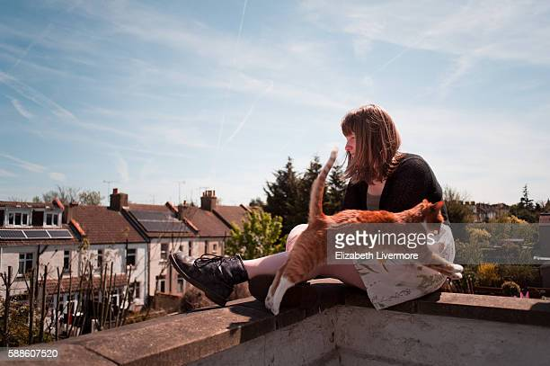 Woman and cat sit on ledge of rooftop terrace