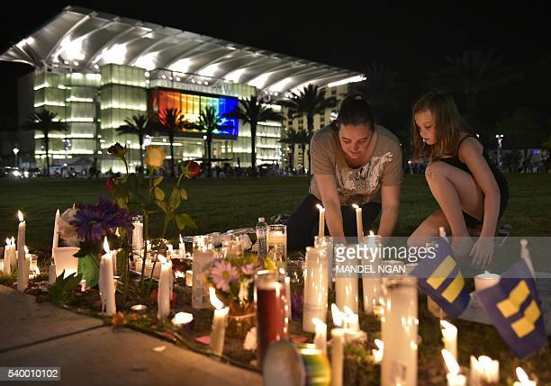 A woman and child arrange candles for the victims of the Pulse nightclub shooting following a vigil on June 13 2016 at the Dr Phillips Center for the...