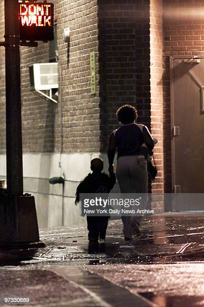 Woman and child arrive at night at the Emergency Assistance Unit on E. 151st St. In the Bronx, the primary homeless intake office. In scenes replayed...