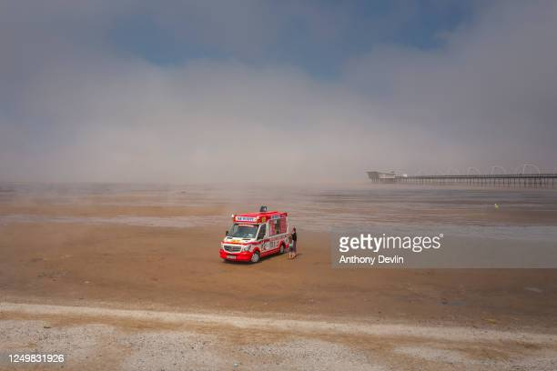 Woman and child buy an ice cream as sea mist blows across the beach at Southport on June 15, 2020 in Southport, England. The British government have...