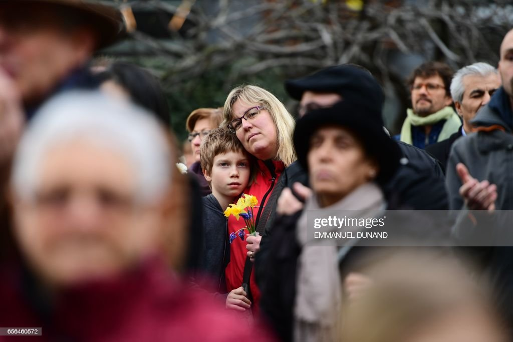 TOPSHOT - A woman and child carry flowers during a commemorative march as Belgium marks the first anniversary of the twin Brussels attacks by Islamic extremists on March 22, 2017 at La Bourse in Brussels. Belgium marks the first anniversary of the Islamic State bombings in Brussels, one at the airport and the other in the metro, in which 32 people were killed and more than 320 wounded with ceremonies showing that the heart of Europe stands defiant. / AFP PHOTO / Emmanuel DUNAND