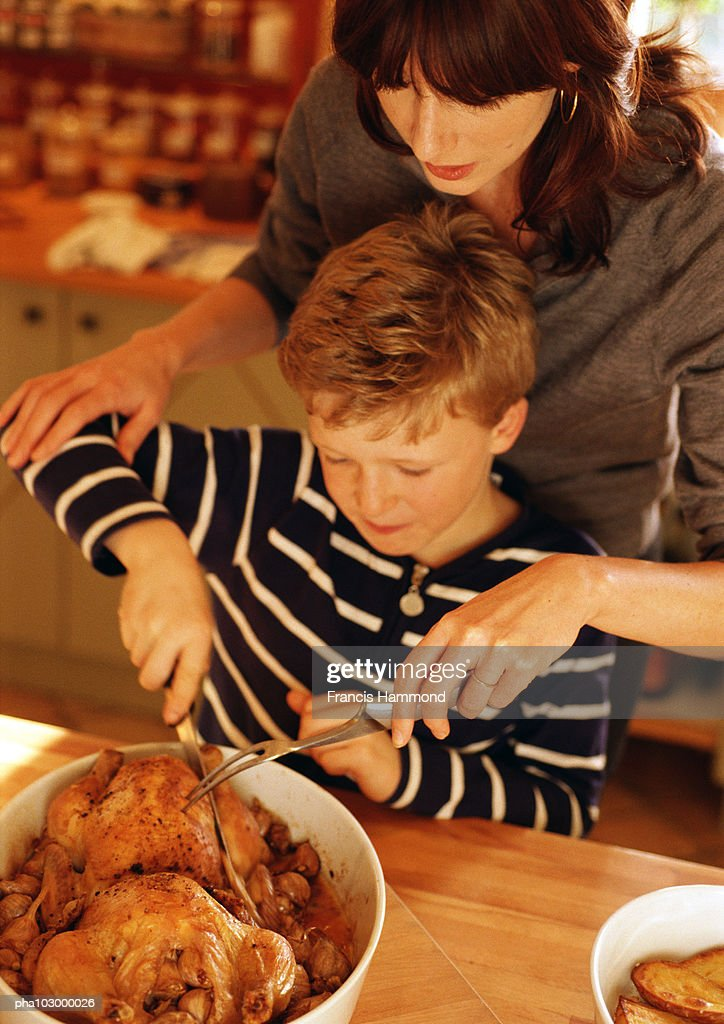 Woman and child carving chickens : Stockfoto