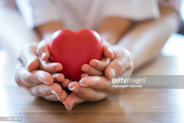 woman and child holding red heart. - social services stock pictures, royalty-free photos & images