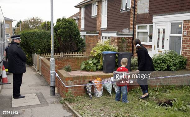 Woman and child lay flowers close to the house on Irvine Drive in Margate, England where the body, believed to be of Dinah McNicol, was found in the...