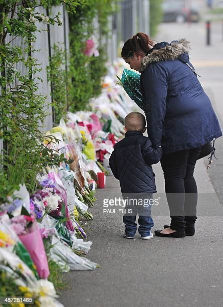 Woman and child leave floral tributes at Corpus Christi Catholic College in Leeds, northern England, on April 29 following the fatal stabbing of a...